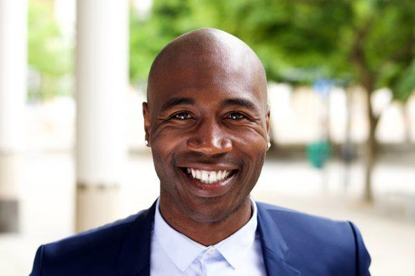 smiling-african-businessman-standing-outdoors-PPMTLXR.jpg