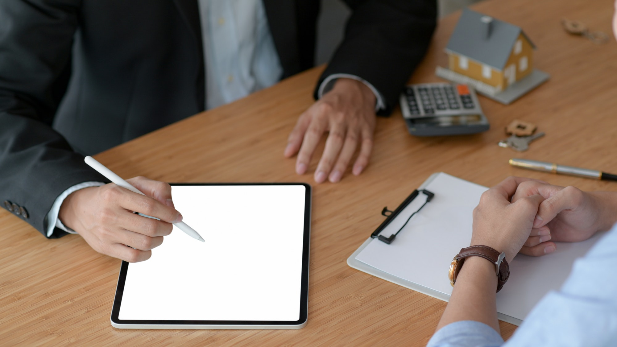 Real estate insurance agents are using tablet to recommend insurance packages to customer.